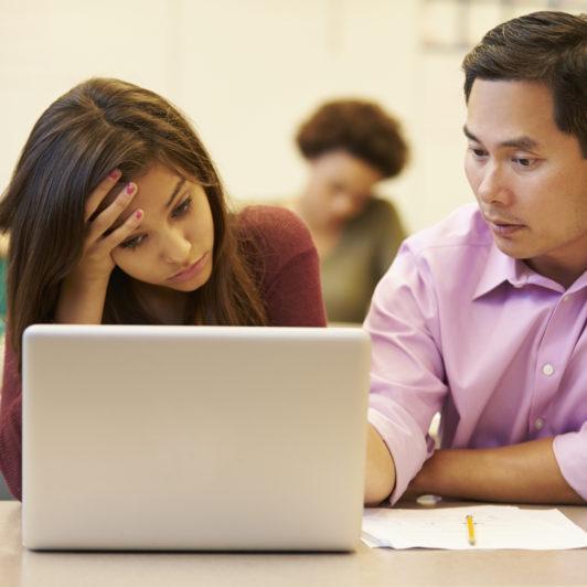 High School Teacher Helping Stressed Pupil In Class